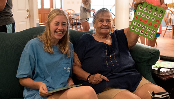 Christ Community Church youth group member Tyndall Cunningham shares a laugh with Maplewood Lane resident Jo Standiford after winning a round in Bingo. (Reporter Photo/Keith McCoy)