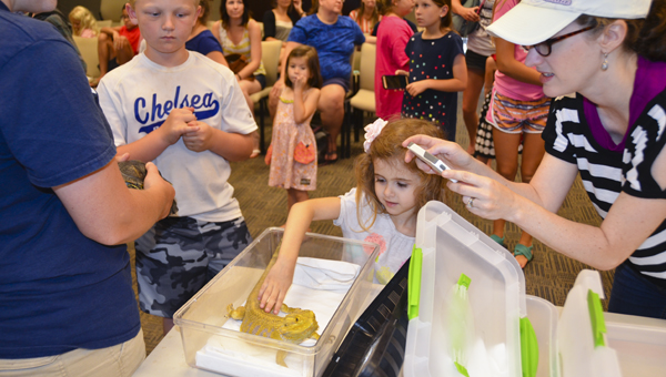 Amelia Ansel pets a desert lizard from the Alabama 4-H Center at the Chelsea Public Library's summer reading program July 6. (Reporter Photo/Emily Sparacino)