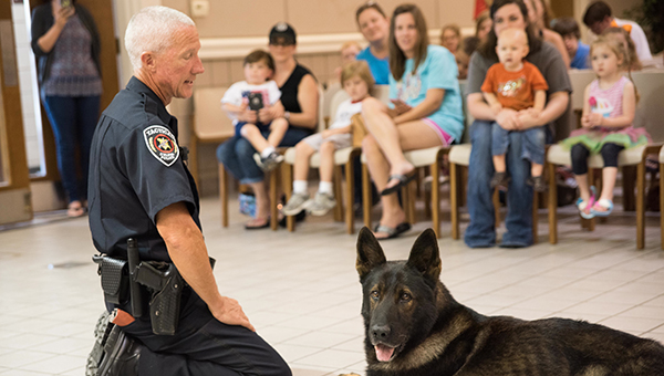 Helena Police Officer and K9 Handler Philip Richards tells children about the department's 10-year-old German Sheppard K9 Bak on Wednesday, July 6. (Reporter Photo/Keith McCoy)