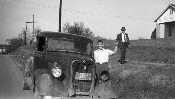 """""""Meet me at the church."""" This circa 1949 snapshot shows Charles """"Bunk"""" Nelson posing beside Mullins Grocery Store's delivery truck in front of the Baptist Church in Helena. Mr. Luther Mullins is standing behind Nelson. (Contributed/City of Helena Museum)"""