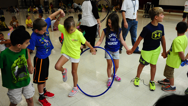 """Inverness Elementary School students, as part of the school year's """"Everday GREAT"""" theme, play a game to learn about teamwork. Students formed a circle and had to pass a hula hoop around the circle without breaking their hand chain. (Photo by Stephen Dawkins)"""