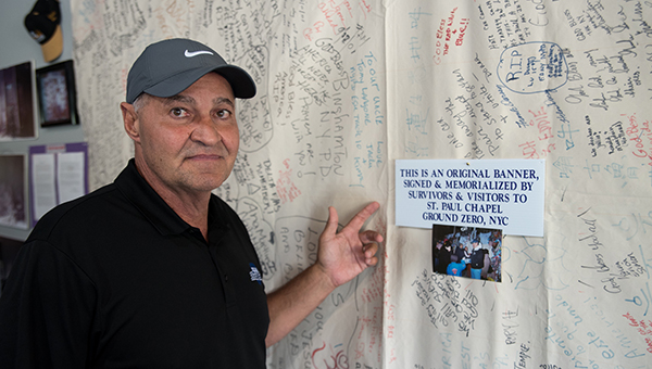 Helena Health Club Owner Terry Brasseale stands beside an original signed banner from Ground Zero in New York City that was signed to honor those in the 9/11 attacks. Brasseale has set up a memorial in Helena Health Club for the 15th anniversary. (Reporter Photo/Keith McCoy)