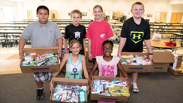 Back row from left, Max Yanez, Caleb Haney, Jill Wilson, Reece Mims and front row from left, Lauren Sawyer and Caitlyn Copeland hold up supplies that have been collected the week of Aug. 15 at Helena Intermediate School that will be shipped to Louisiana to help flood victims. (Reporter Photo/Keith McCoy)