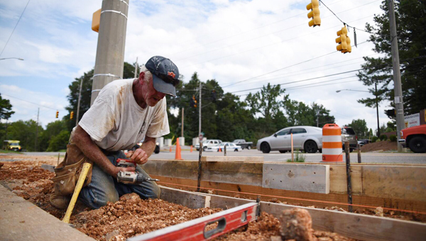 A Global Management Group employee works to complete a project to renovate the entrance to the parking lot at Warrior Park's Field B in late August. The new entrance has now been opened to traffic. (File)