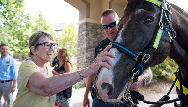 Danberry at Inverness resident Elka Joost pets Slade while Birmingham Police Department mounted unit officer Brad Herndon looks on.