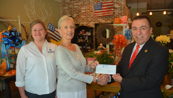 Kelly Burley, left, of Main Street Florist in Mt Laurel and Sunny Gilliam presented a check for $1,403 to Shelby County Sheriff John Samaniego after more than 275 blue and black bows were sold as part of a fundraiser. (Photo by Stephen Dawkins)