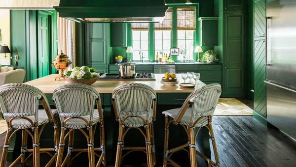 The 2016 Southern Living Idea House's kitchen, doused in a rich shade of dark green, draws natural elements inside with neutral-colored woven shades, countertops and stools.
