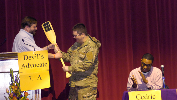 The coveted Oar, being passed to a new recipient, is the University of Montevallo Life Raft Debate's version of a trophy. The winner of the debate each year is given the Oar, which bears the names of past winners. (Contributed)