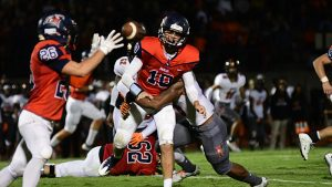 Oak Mountain quarterback Jackson Kimbrell (10) passes as he is hit to Daniel Salchert (26) during the Eagles' 49-6 loss to the Buccaneers on Sept. 30. (Reporter Photo/Neal Wagner)