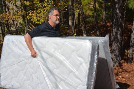 Bedzzz Express Vice President David Riddle carries two mattresses into the Residential Center. (Reporter photo/Briana Harris)