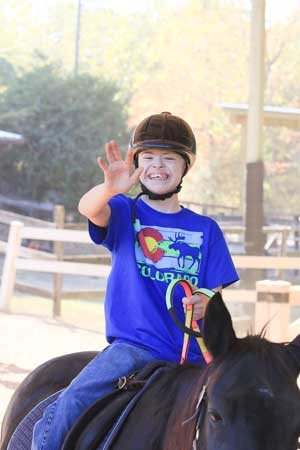 A child waves while riding one of the horses at Special Equestrians