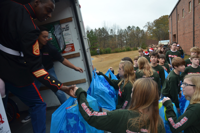 OMMS NJHS students help U.S Marine Corps Staff Sgt. Michael Tucker and other Toys for Tots representatives load a truck with toys.