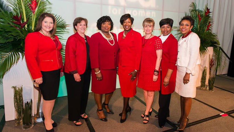 Casi Ferguson, far right, dons a white suit at a Go Red for Women luncheon to denote she is a survivor. Ferguson underwent quadruple bypass heart surgery in 2014.