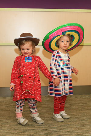 Noelle and Hannah Baxter don hats during a visit to their dad's clinic.